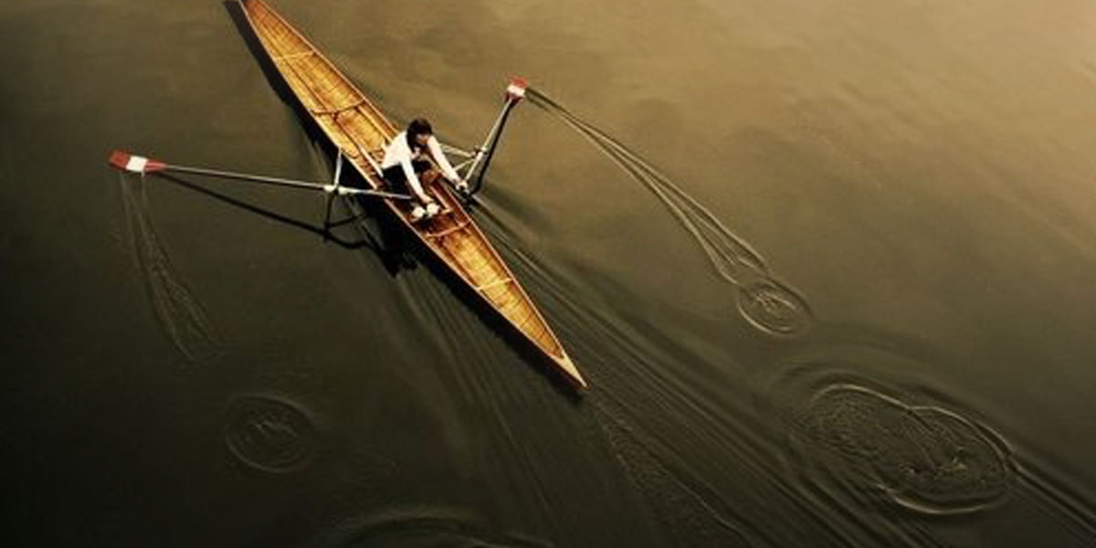 An overhead view of a sculler rowing on the water